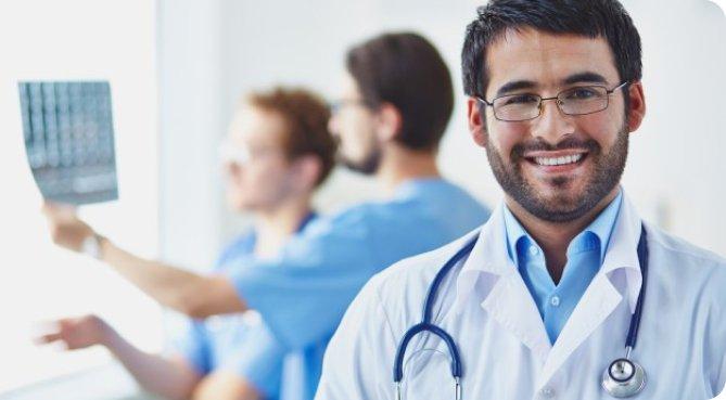 Un doctor sonriendo y otros doctores viendo una radiografia en el fondo