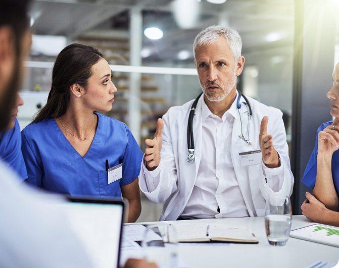 un doctor de avanzada edad hablando con su equipo